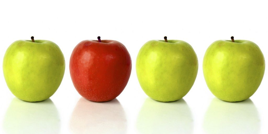 green apple with the red one standing out from the crowd - over a white background with reflection